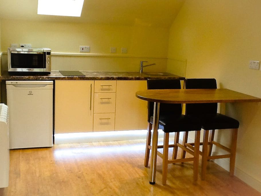 Kitchenette with hob, microwave, fridge,sink, toaster, kettle.  Breakfast bar with electric and wifi sockets.