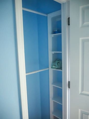 Closet with shelves, extra blankets, hangers are provided.