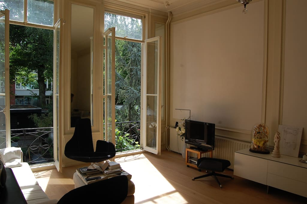 Sunny living with high sealings and large windows on garden