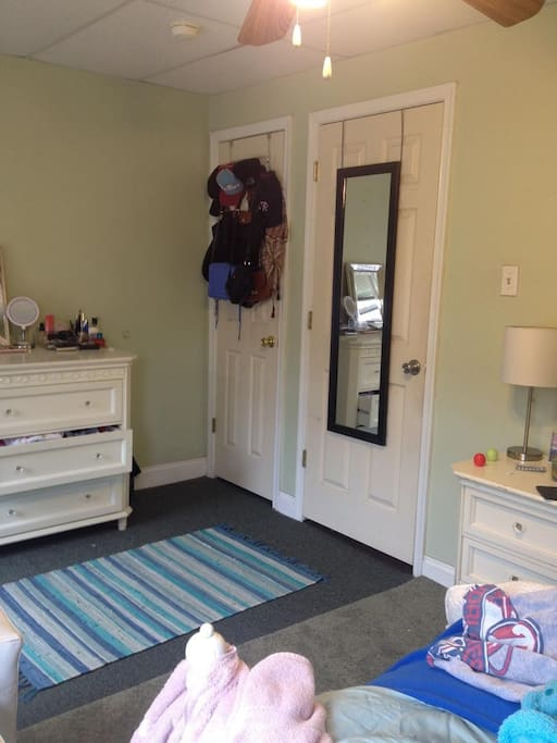 Large room with dresser, closet, and mirror.