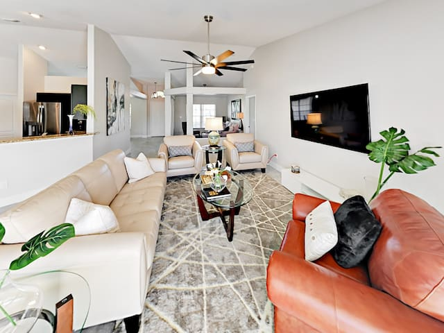 """Unwind in the sunny living room with seating for 6 and a 65"""" flat-screen TV."""