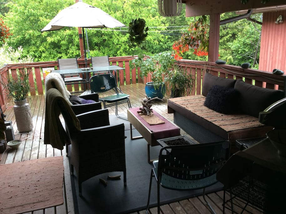 Gorgeous covered outdoor living room patio with bbq. Surrounded by greenery.
