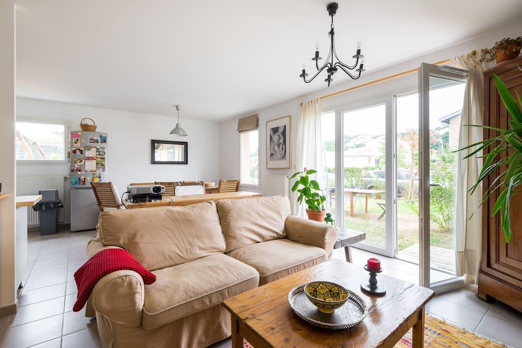 Pièce à vivre avec coin salon, table à manger et cuisine ouverte, baie vitrée sur le jardin.