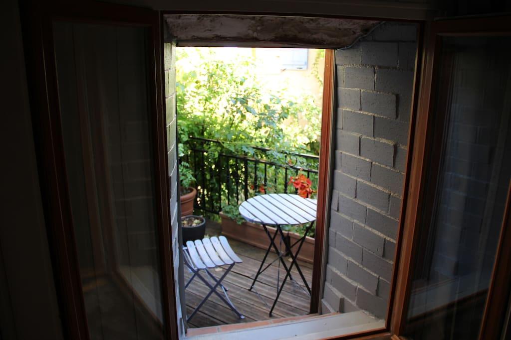 Vue de la chambre sur le petit balcon et la cour intérieure