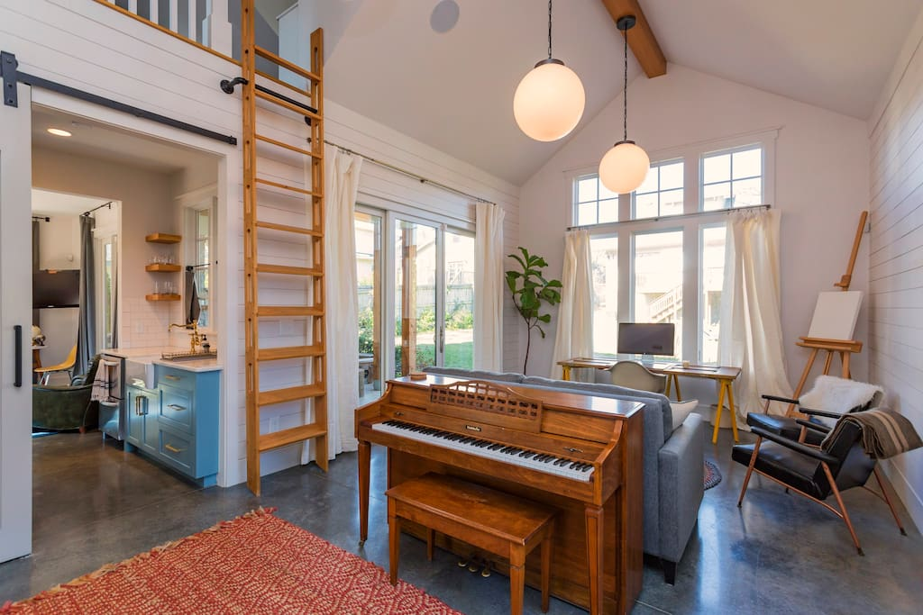 Main common area with Crate & Barrel sofa bed and ladder going up to loft. The ladder is operated by pulling the base away from the wall and then climbing up! The barn door separates this room from the rest of the house. (NOTE: sadly the piano was recently sold)
