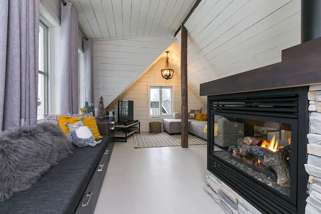 Aménagé sous les combles d'une célèbre maison centenaire, salon avec foyer au gaz
