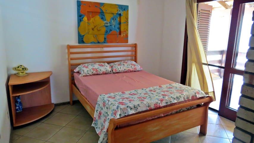 Quarto com cama de casal e sacada com vista para o mar.