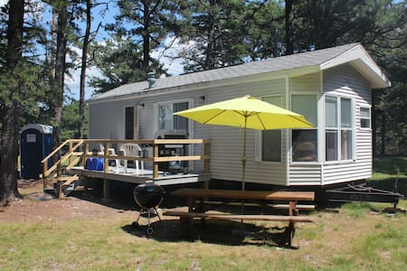 Our primitive RV with 1 bedroom, Full kitchen & living room included an HDTV with local channels, Netflix, Amazon Video. Free WiFi included, and a laptop computer for your use. Outside deck with gas grill & seating. Fire pit, picnic table too!
