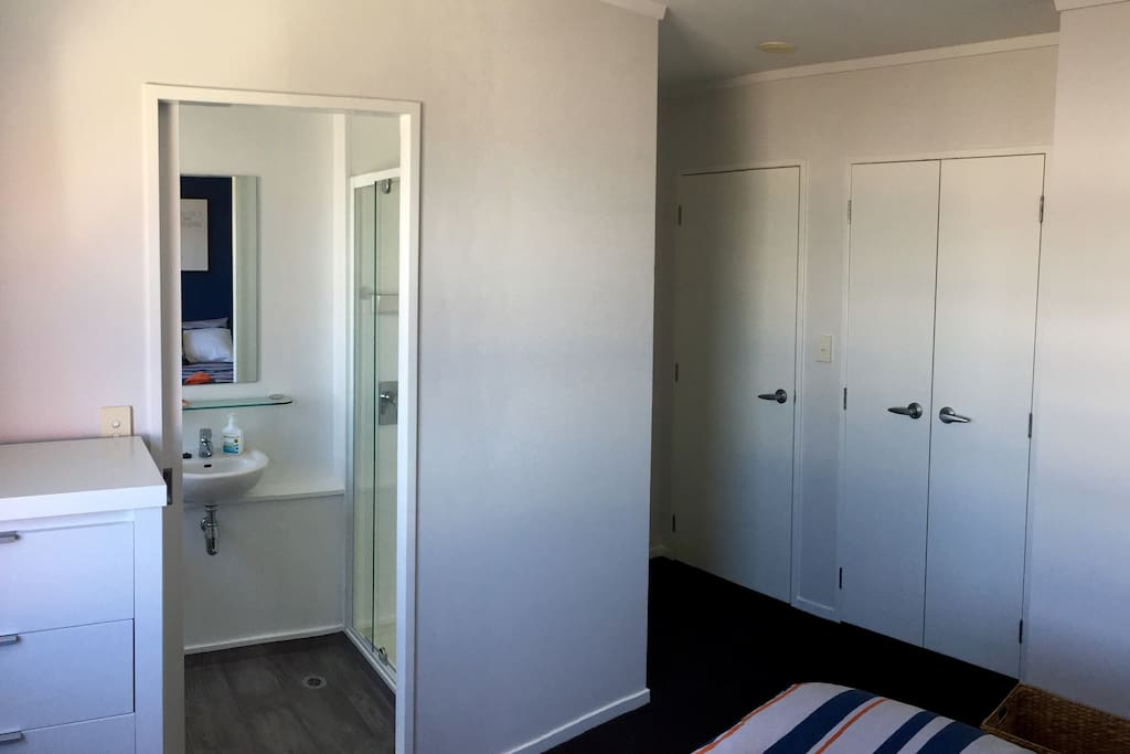 Ensuite bathroom, with generous wardrobe (double-doors on the right).