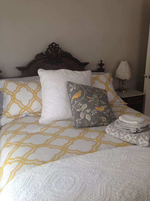 Comfortable double bed with antique headboard