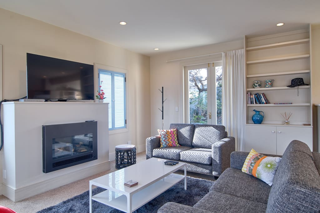 Lounge area - sun soaked room with new modern furnishings. One side opens up to a gorgeous garden are, the other opens out on to your private front yard overlooking the golf course and mountains! Turn the fire on at night or in winter for a cozy setting!