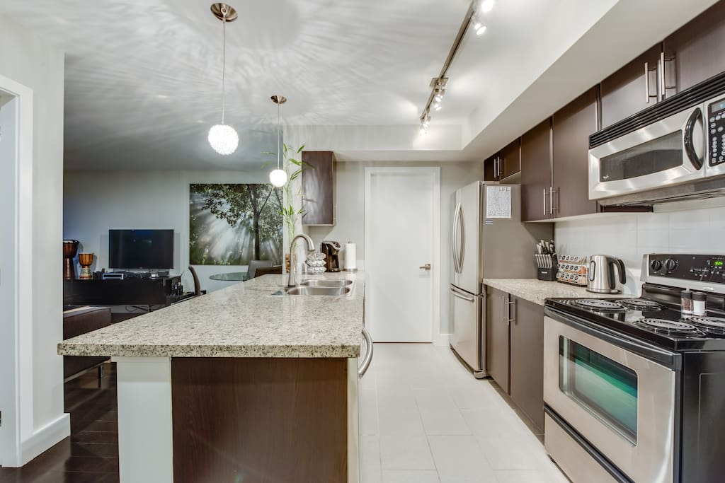 Fully equipped open concept kitchen with stainless steel appliances