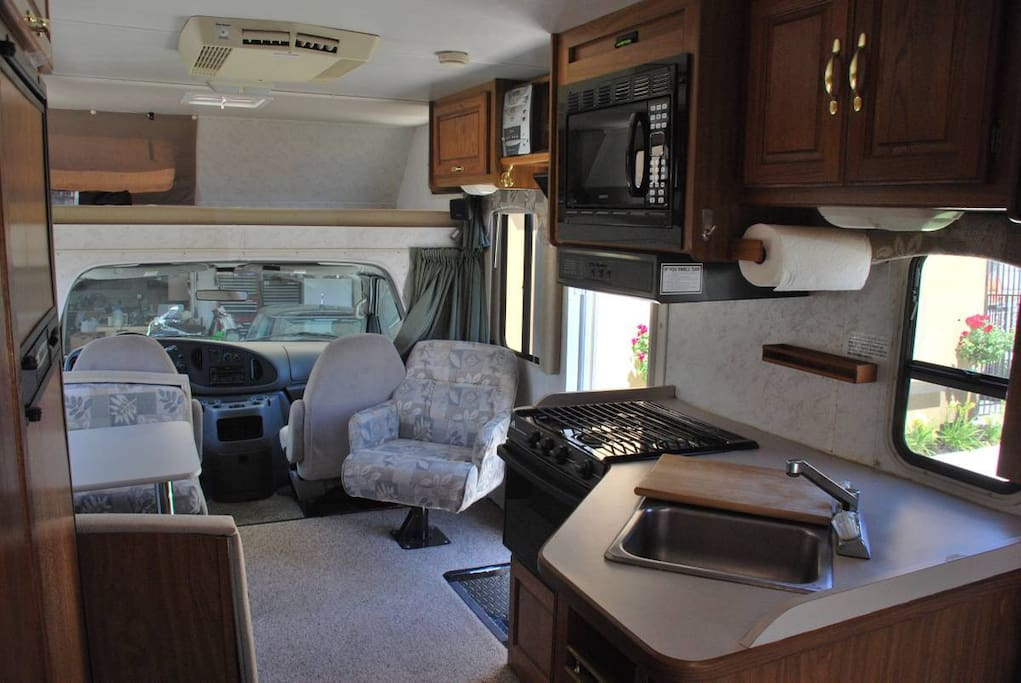 Full kitchen and living area. Above the driving cab is a king sized bedroom area.