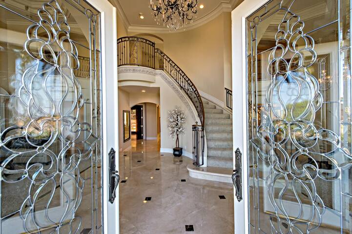 Double glass doors leading to a grand entrance hall with beautiful staircase