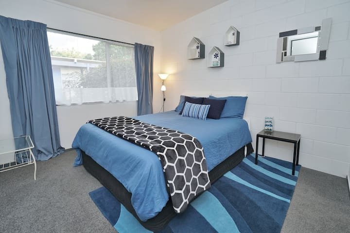 Bedroom with queen bed and four pillows