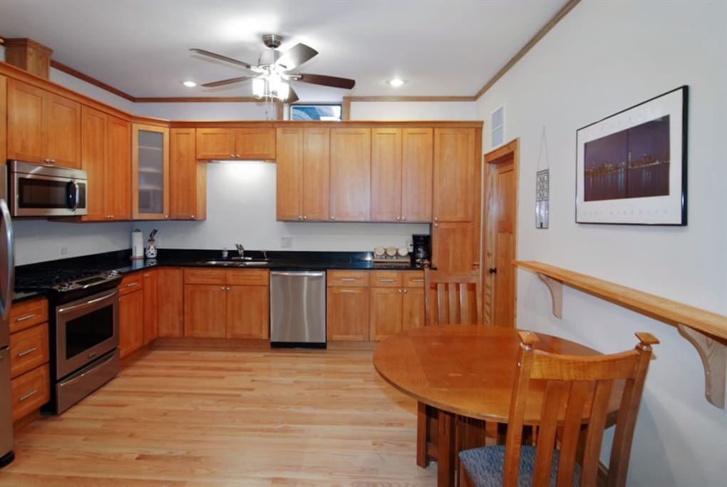 Large kitchen with breakfast table. Fully stocked for all your cooking needs.  Laundry in room next to kitchen.