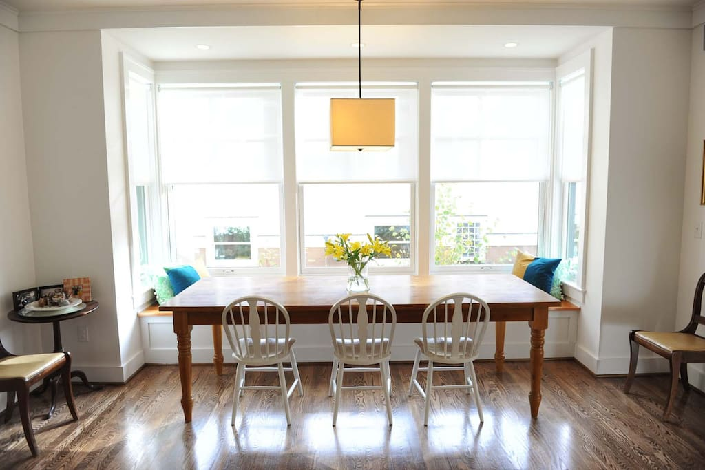 The dining area with a farm table and cozy window bench.