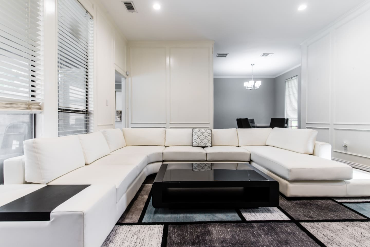 large open living room with with a small bar wine fridge and a large 80 inch smart tv and sound bar
