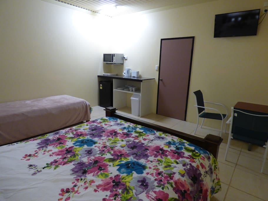 Unit Room with queen bed, single bed, TV, microwave, bar fridge, jug, toaster and small table.