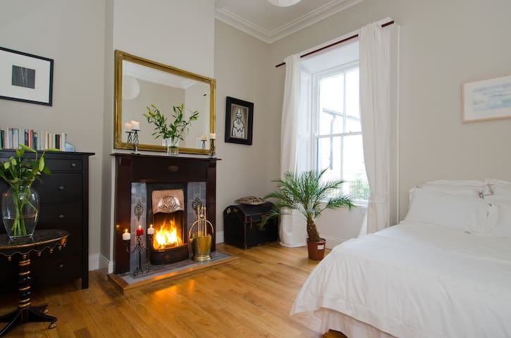 Spacious double bedroom with feature fireplace and high ceiling, oak floor