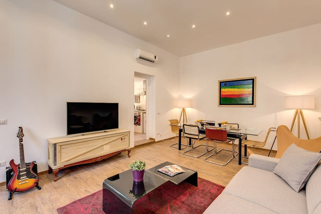 The living room with the sofa - bed, the big glass table for 8/10 people and the smart tv
