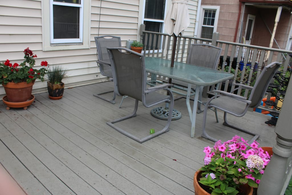 Rear deck with planters and six-person outdoor table with umbrella