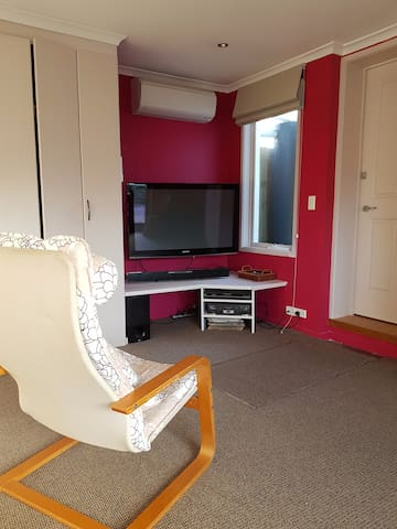 TV corner with comfortable chairs and air conditioner/heater unit.