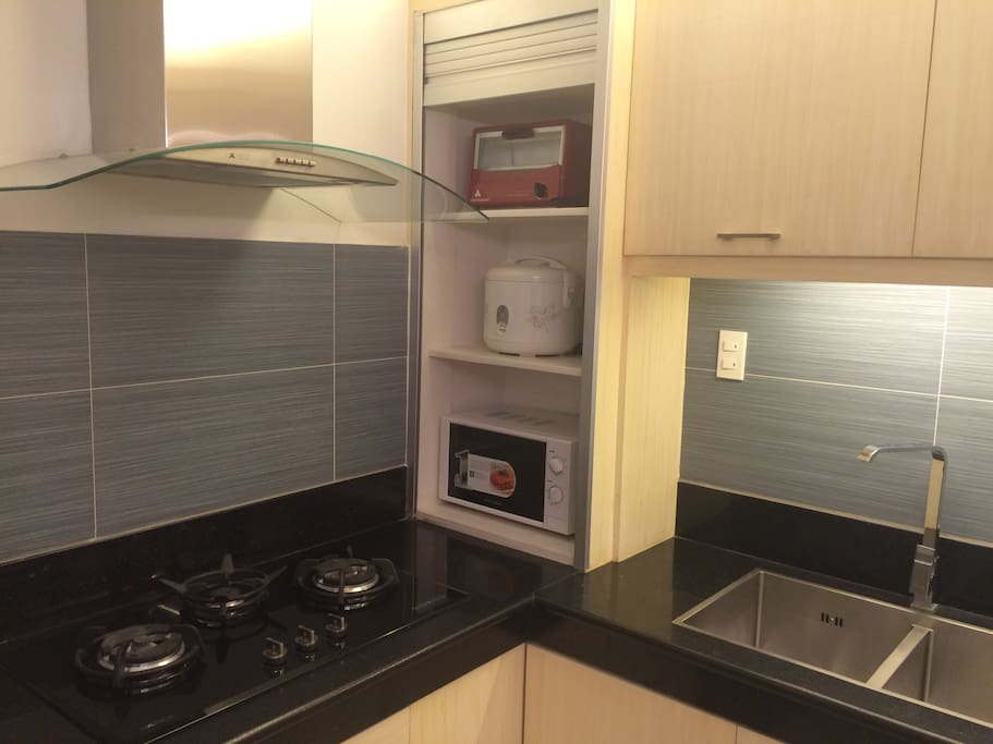 Kitchen complete with utensils, pots, microwave, oven toaster, fridge & rice cooker
