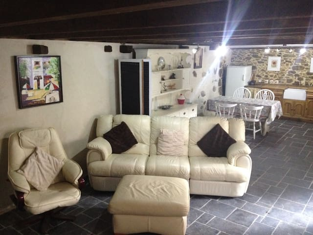 Comfortable open plan living area with reclining chairs and log burner.