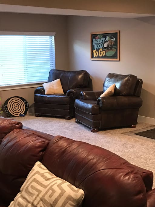 Just inside the separate entrance to your downstairs suite, the spacious living room has 2 large leather chairs, couch and loveseat.