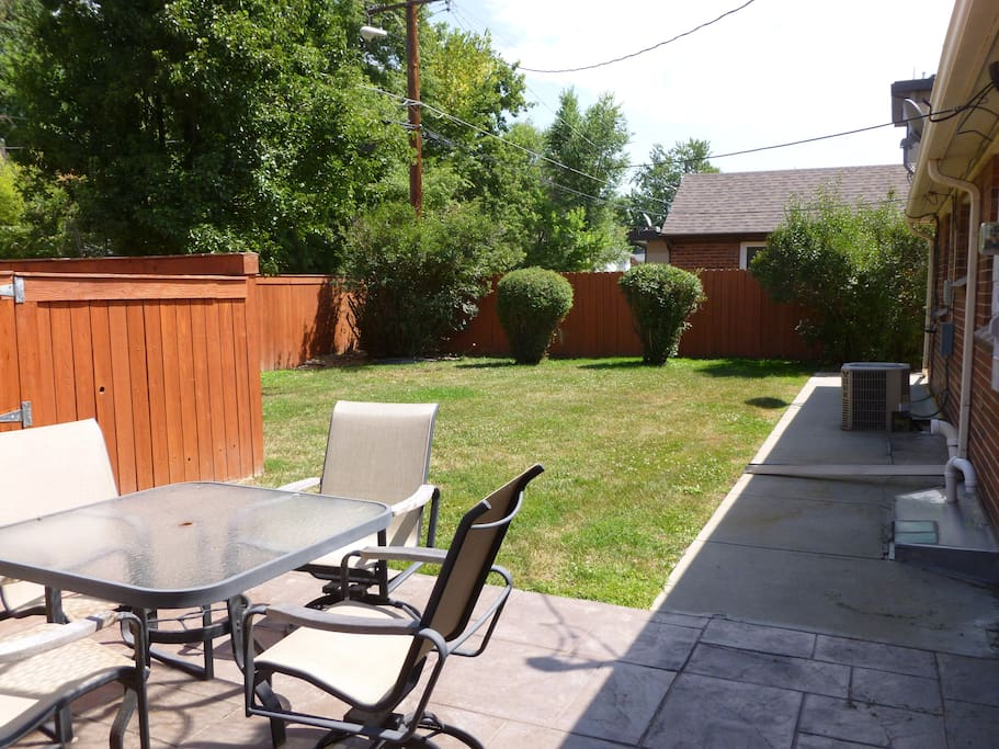 Fenced in back yard with a patio and grill