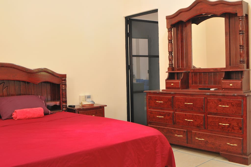 The room, with king-sized bed and beautiful ornate dresser. Also includes television and air conditioning unit.