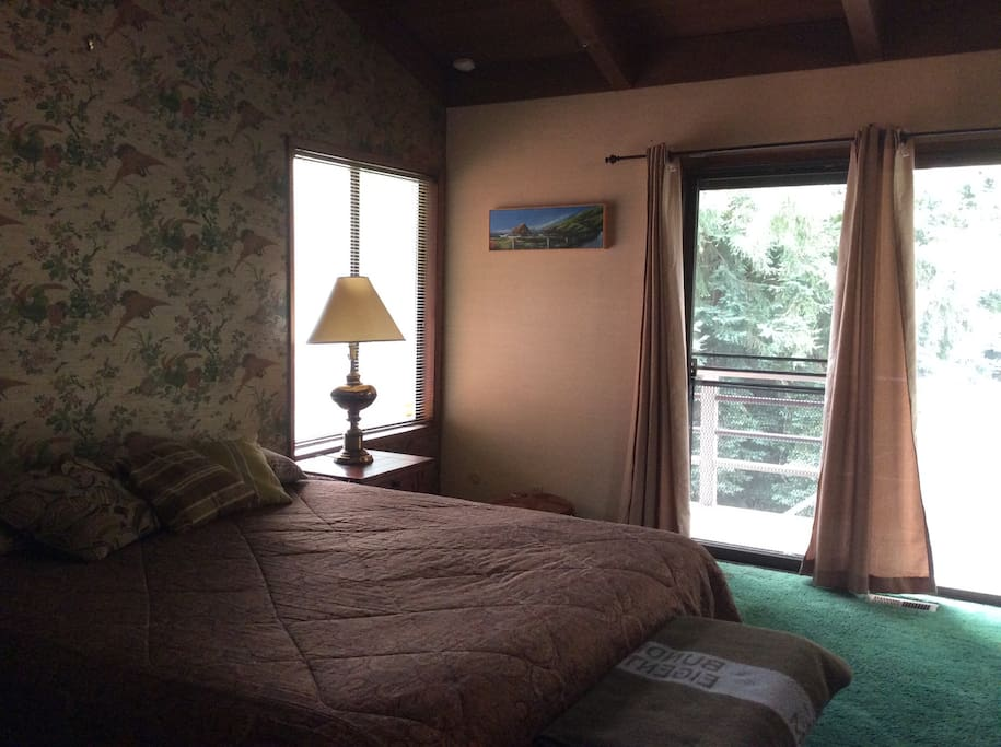 Master bedroom, with access to wrap around deck and the lower balcony.