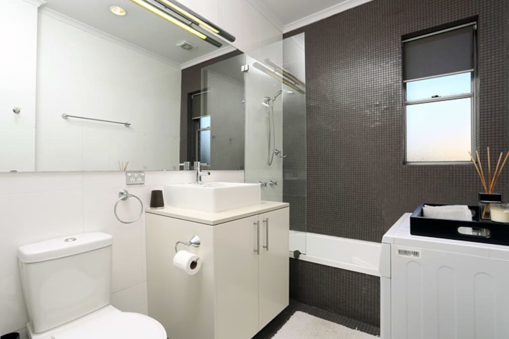 Large spacious bathroom with deep bathtub and laundry facilities (washing machine and dryer)