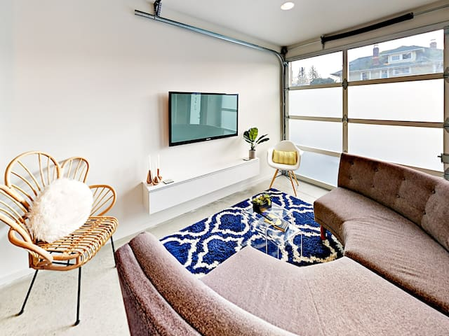 """The sun-soaked living room has a 50"""" Roku TV and a garage-style door for seamless indoor-outdoor living."""
