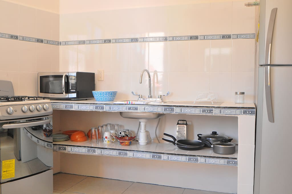 Fully equipped kitchen with fridge-freezer, oven, microwave, and all cooking utensils.