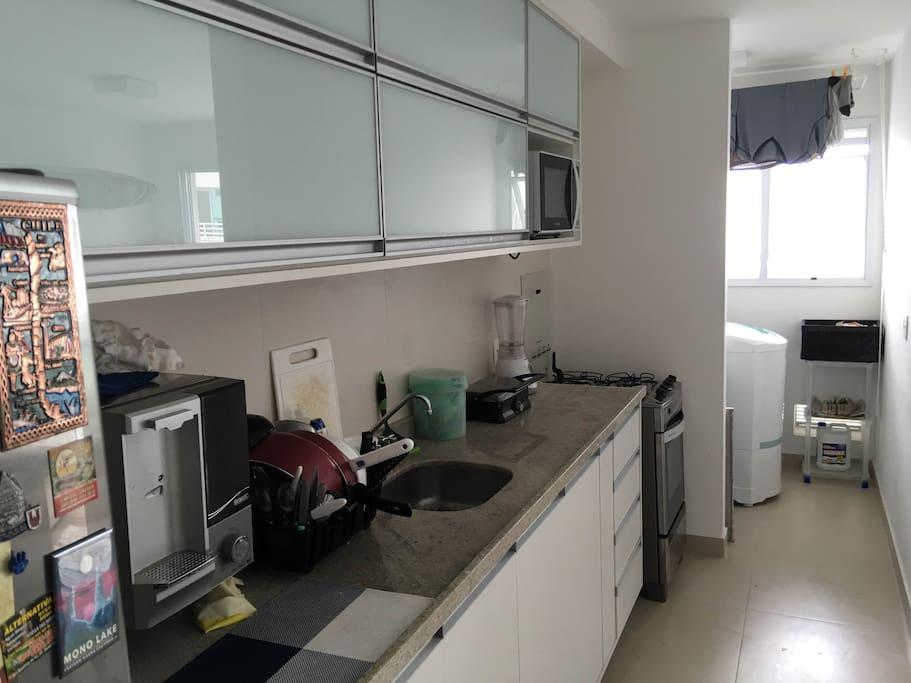 Cozinha equipada com Micro-ondas, Forno, Geladeira, Sanduicheira, Máquina de Lavar, Filtro de Água e utensílios.