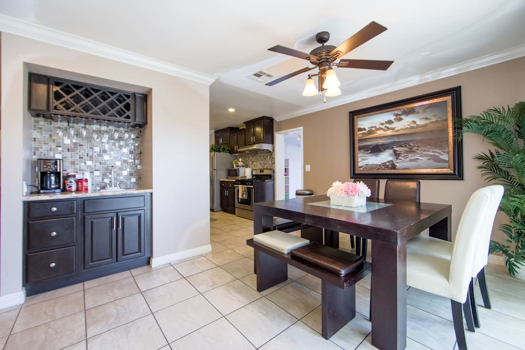 Open floor plan with wine bar and large dining table.