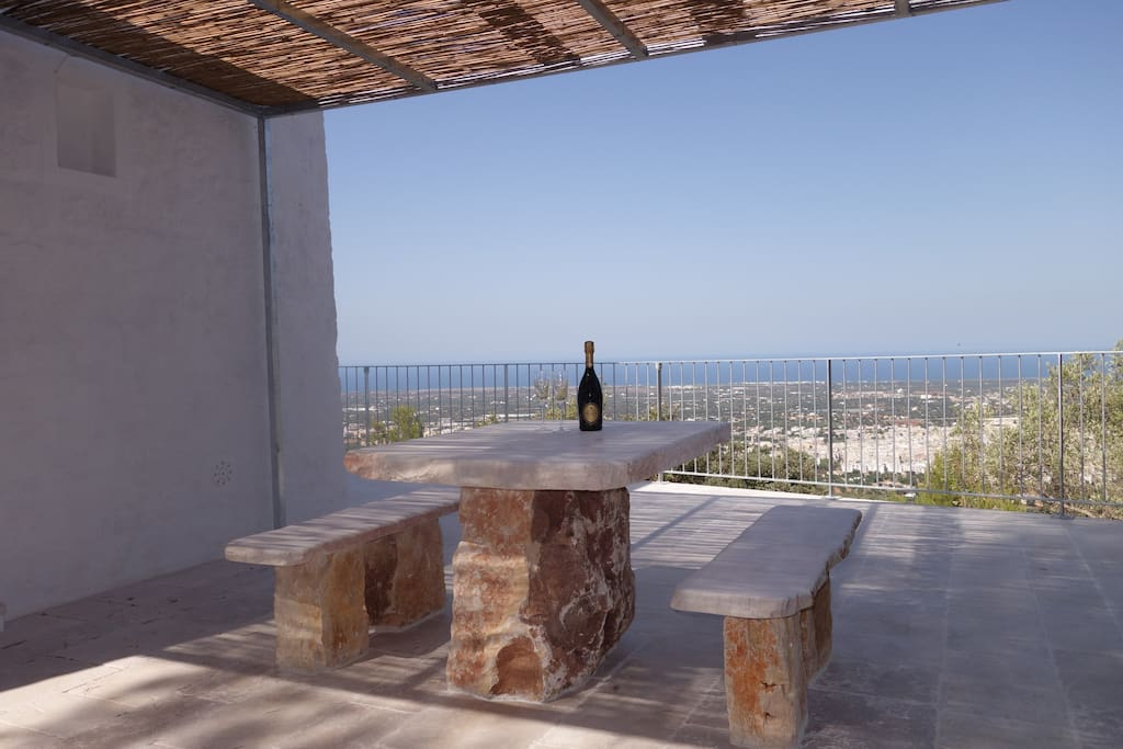 The pergola and terrace area with natural stone table and benches