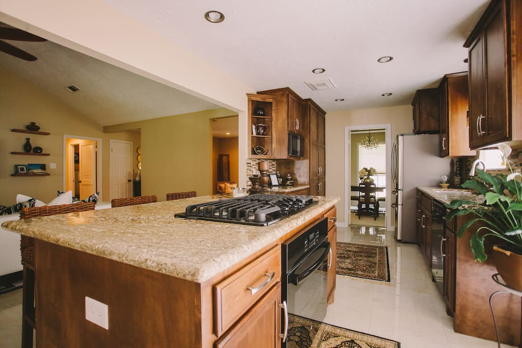Island kitchen with gas range, oven , microwave and coffee maker.