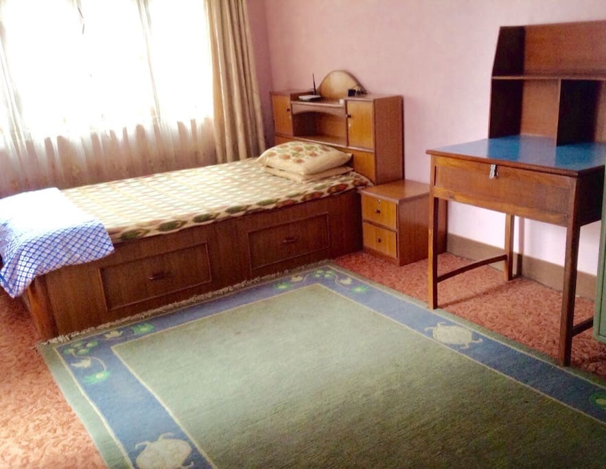 A bedroom with a king size single bed and a table