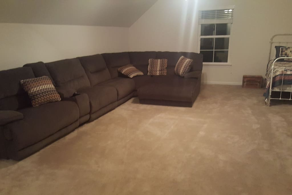 bonus room with sectional and twin bed