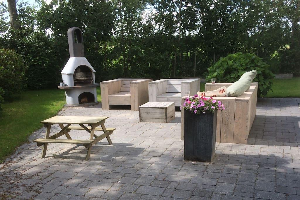 Terras met loungebanken en buitenhaard / BBQ