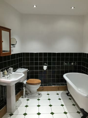 Bathroom with deep roll-top bath & separate rain shower cubicle (not visible)