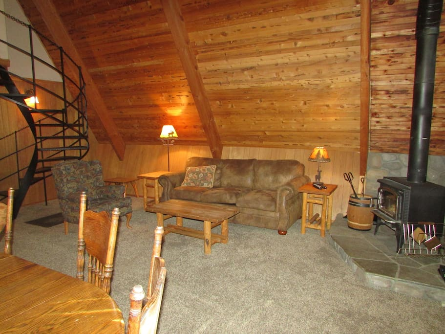 great room with soaring cedar ceilings, wood stove and nice furnishings