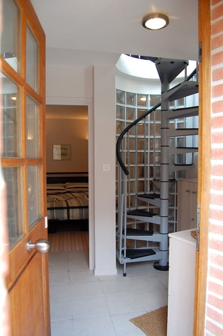 View through front door, showing spiral staircase up to living room, and bedroom behind