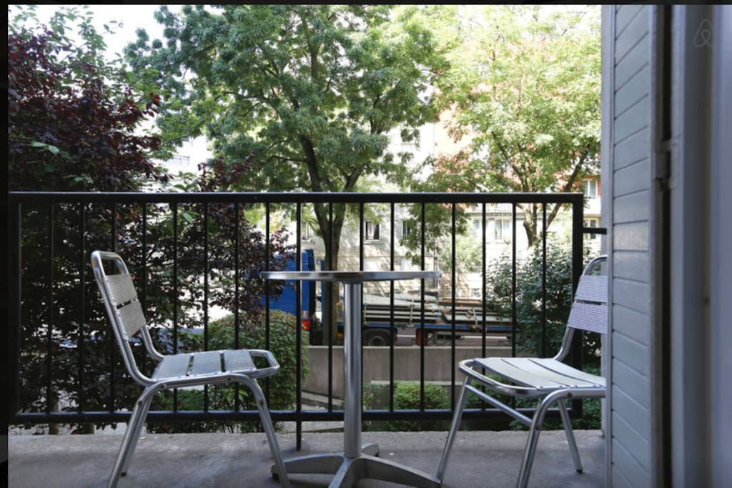 Lovely balcony overlooking some trees with a bistrot table and chairs.