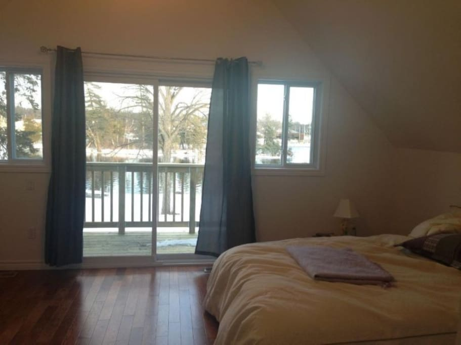 Beautiful master bedroom with balcony which overlooks the Otonabee River.