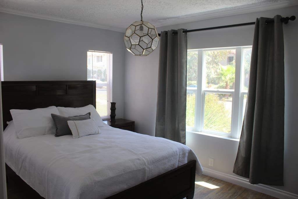 Stunning bright and modern bedroom, with a plush queen sized bed and a beautiful street view.