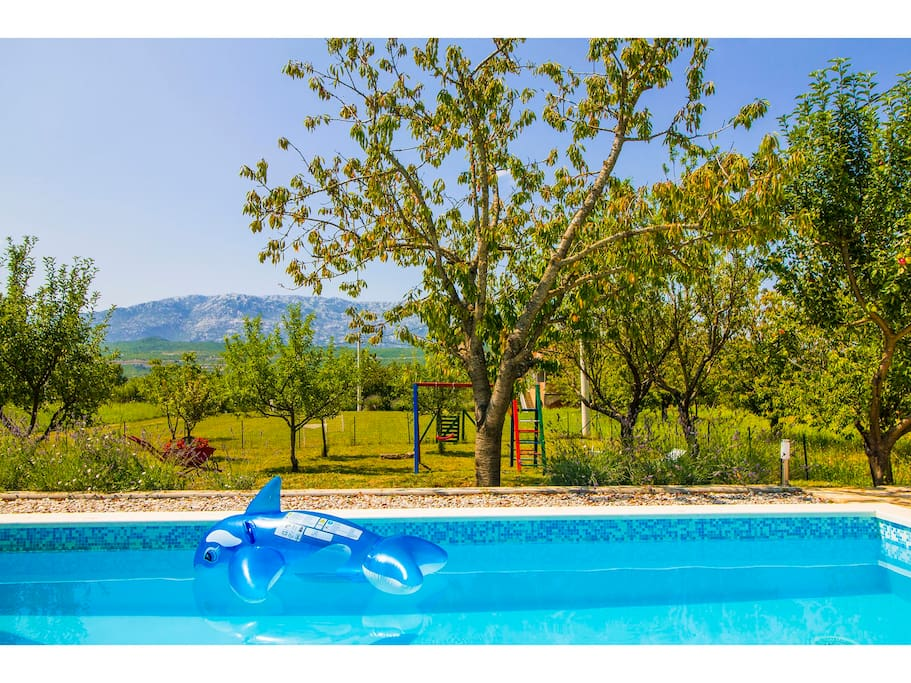 View on pool , mountain and play garden in front of  house